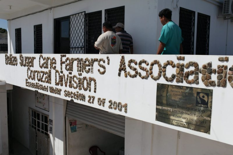 "The facade of the Belize Sugar Cane Farmers Association (BSCFA) office in Corozal displays a plaque that reads: ""Building Inauguration Funded with Fairtrade Funds on February 14th, 2011."""